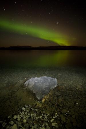 northern light: Intense northern lights (Aurora borealis) over Lake Laberge, Yukon Territory, Canada, with rock on lake shore.