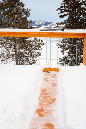 winter escape: Footsteps of person trying to escape winter by jumping over railing of snow covered wooden deck. Stock Photo