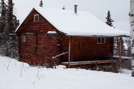 log cabin in snow: Snowflakes falling on cozy winter cabin inviting you to spend your Christmas holiday. Stock Photo