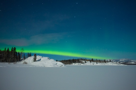 Northern Lights (Aurora borealis) over moon lit snowscape of frozen lake and forested hills. Stock Photo - 8636488