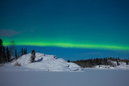 Northern Lights (Aurora borealis) over moon lit snowscape of frozen lake and forested hills. Stock Photo - 8636524