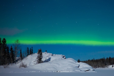 Northern Lights (Aurora borealis) over moon lit snowscape. Stock Photo