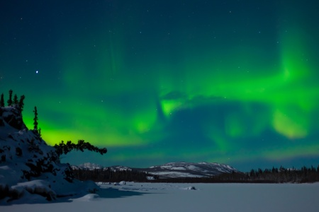 green light: Northern Lights (Aurora borealis) over moon lit snowscape of frozen lake and forested hills.