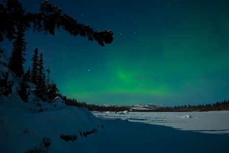 northern light: Northern Lights (Aurora borealis) over moon lit snowscape of frozen lake and forested hills.
