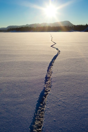 crack: Wide crack in snow-covered ice surface of frozen lake.