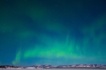 Northern Lights (Aurora borealis) over moon lit snowscape of frozen lake and forested hills. Stock Photo - 8720606