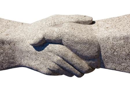 manos unidas: Escultura de granito de estrechar la mano aislado sobre fondo blanco.