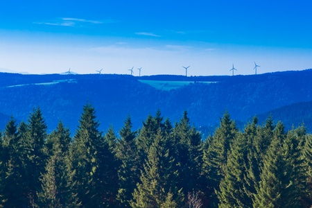 Forested landscape with windfarm at horizon in Black Forest, rural Germany. photo