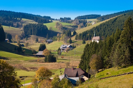 Farmland, farmhouses with chapel and forested hills in Black Forest, rural Germany. photo