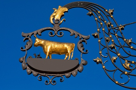 Beautifully crafted wrought iron sign with golden ox with empty copyspace for your message. photo