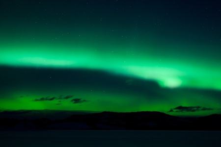 Green northern lights (aurora borealis) substorm above silhouette of hills and clouds. Stock Photo