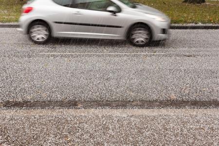 Kleines Auto fahren auf die Stra�e durch schwere Hagel Sturm.