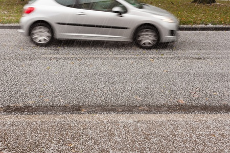 Small car driving on road through heavy hail storm. Stock Photo