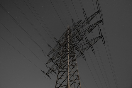Steel pylon of high voltage electric power transmission line at moon lit night. photo