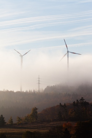 Ghostly shapes of large wind turbines dwarfing pylon of high-voltage transmission line on foggy morning in Eifel, rural Germany, Europe.