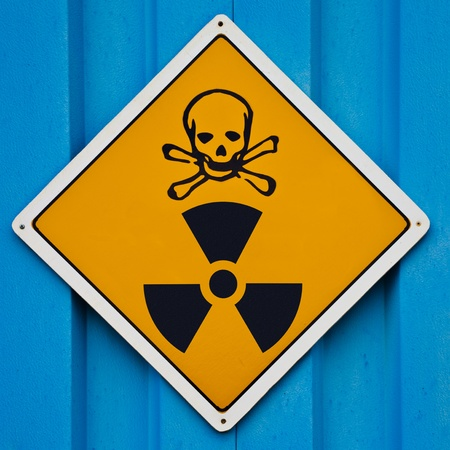 plutonium: Deadly nuclear radiation warning sign with skull and crossbones on blue background. Stock Photo