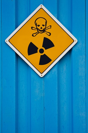 Deadly nuclear radiation warning sign with skull and crossbones on blue background. photo