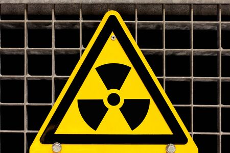 bolted: Nuclear radiation warning sign bolted to steel grid Stock Photo