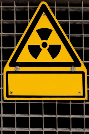 bolted: Nuclear radiation sign bolted to steel grid with blank copyspace for your message.
