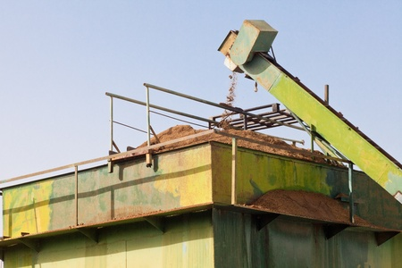 Exhausted olive pulp (orujo) from busy olive oil mill factory being conveyed into huge metal silo container for later composting. Stock Photo - 9167853