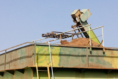 Exhausted olive pulp (orujo) from busy olive oil mill factory being conveyed into huge metal silo container for later composting. Reklamní fotografie