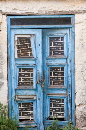 Peeling blue paint on exterior entrance door of abandoned building, in desperate need of major renovation job. photo