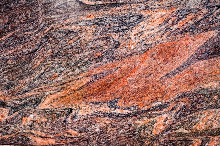 inclusions: Beautiful texture of red-colored natural granite. Stock Photo