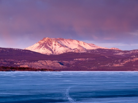 Blue ice of frozen Lake Laberge, Yukon Territory, Canada, with Mt. Laurier on eastern shore glowing red in sunset light. photo