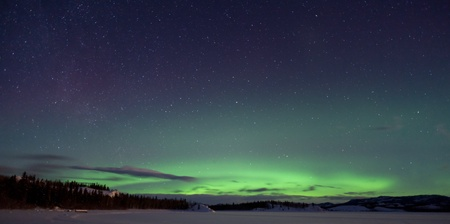 Green northern lights (aurora borealis) substorm, a few clouds and lots of stars on night sky above snowy hills. Stock Photo