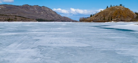 frozen lake: Distant Skier on vast ice surface of huge frozen Lake Laberge,  Yukon Territory, Canada, in April.