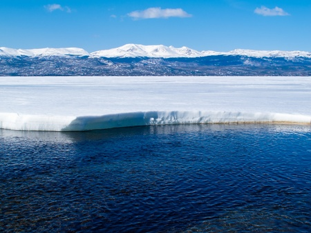 First open water at thawing Lake Laberge, Yukon Territory, Canada, and snow-covered mountains at distant shore of ice-covered frozen lake.