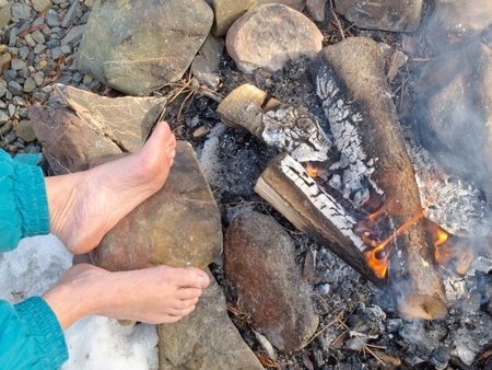 Bare feet of one person are warming at a Campfire outdoors at wintertime with patches of snow. photo