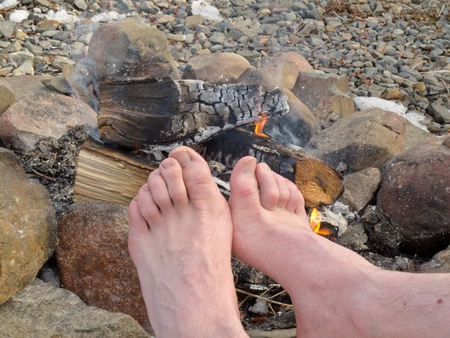 male age 40's: Bare feet of one person are warming outdoors at a Campfire.