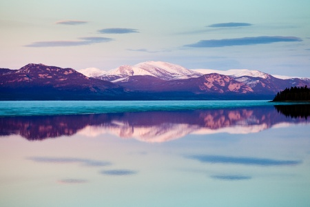 호수 Laberge, 유콘 테리토리, 캐나다에서 얼음 휴식 전에 저녁 : 아직도 주로 얼음 덮인 호수의 진정 열려 물 표면에 눈이 덮여 산의 반영.