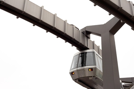 Modern public transportation system Sky-Train hanging from elevated guideway beam on columns isolated on white background photo