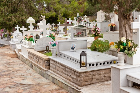 Typical Greek-orthodox cemetery in Greece, Europe, with flowers and images of loved ones (blurred) on graves.