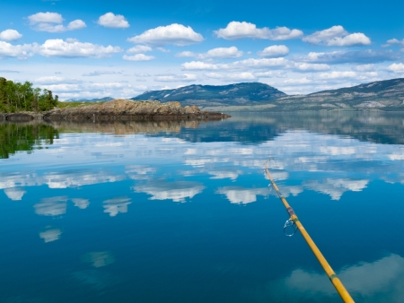 Fishing rod bends under weight of fish that just took lure in Lake Laberge, Yukon Territory, Canada Stock Photo - 9901386