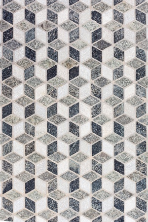 Black and white stone tile mosaic geometric pattern forming 3-dimensional cubes illusion.