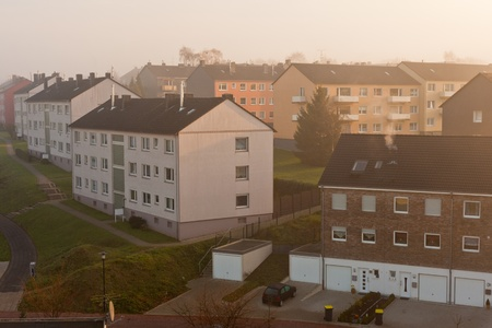 Morning fog in typical German small city suburb of apartment buildings (Germany, Europe). Stock Photo - 10097656