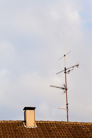 Old-fashioned analogue tv antenna on ceramic shingle rooftop. Stok Fotoğraf