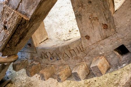 Detail of ancient wooden gear wheel  in old greek wind mill.
