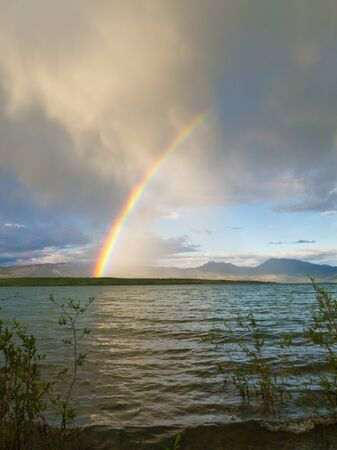 resulting: Summer Thundershower resulting in a rainbow over pristine Lake Laberge, Yukon Territory, Canada.