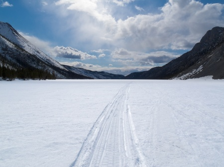 Ski-doo track on windblown snowy surface of frozen mountain lake in winter wonderland of Yukon Territory, Canada Archivio Fotografico