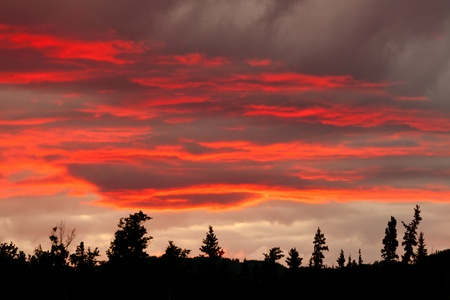 Bewölkt, Sonnenuntergang, Himmel brennt über Silhouette von bewaldeten Hügeln. Standard-Bild
