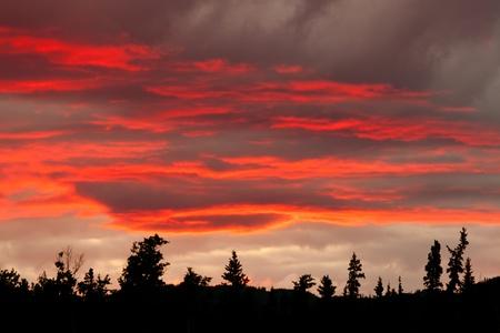 Bew�lkt, Sonnenuntergang, Himmel brennt �ber Silhouette von bewaldeten H�geln.