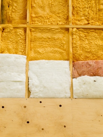 Different types of building insulation: polyurethane spray foam and fiberglas mats. Stock Photo