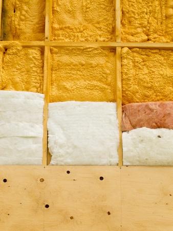 Different types of building insulation: polyurethane spray foam and fiberglas mats. Stockfoto