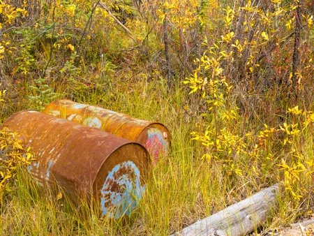 Environmental hazard: Metal drums with unknown content are rusting dicarded in fall colored nature. Stock Photo