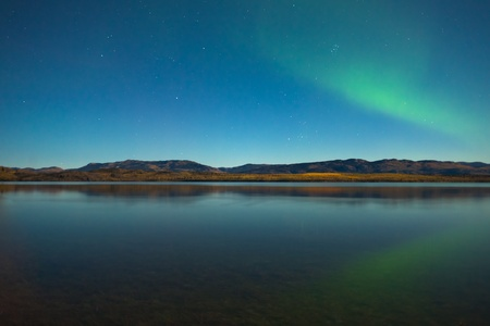 moonlit: Northern lights (Aurora borealis) in moonlit night over Lake Laberge, Yukon, Canada, in fall.