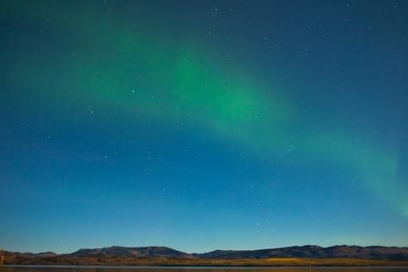 aurora borealis: Northern lights (Aurora borealis) in moonlit night over Lake Laberge, Yukon, Canada, in fall.